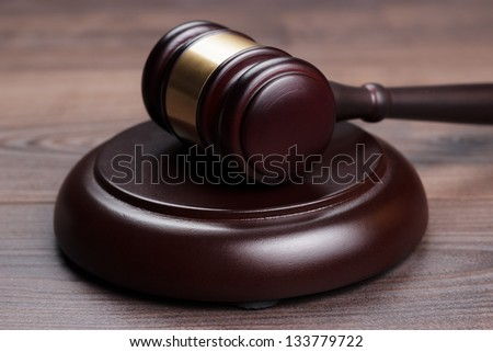 judge gavel on the brown wooden table - stock photo