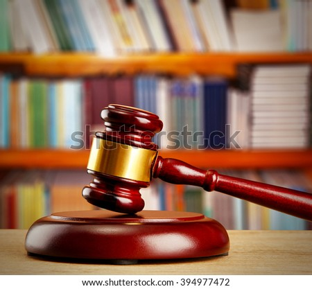 Judge gavel on wooden table on book shelves background - stock photo