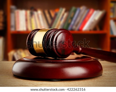 Judge gavel on wooden table on book shelves background