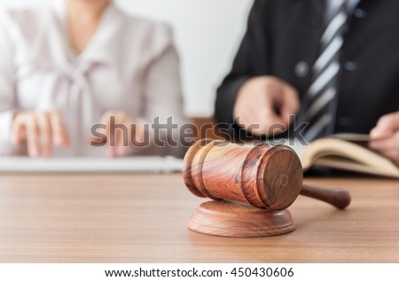 Judge gavel with lawyers having team meeting at law firm in background. Concepts of law,legal advice and services,online auction. - stock photo