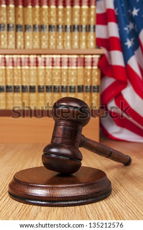 Judge gavel with legal books and American flag in the background - stock photo