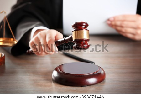 Judge hitting gavel with paper at wooden table closeup - stock photo