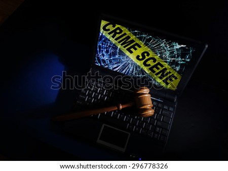 Judge's court gavel on a laptop with crime scene image on broken screen                                - stock photo