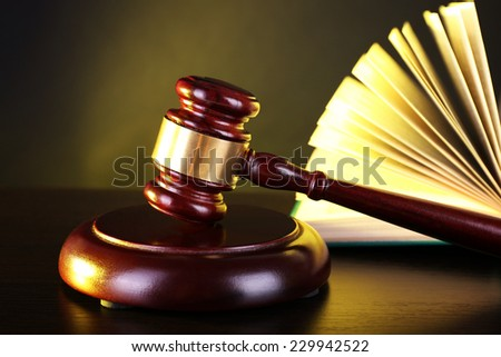 Judge's gavel and open book on yellow and grey background