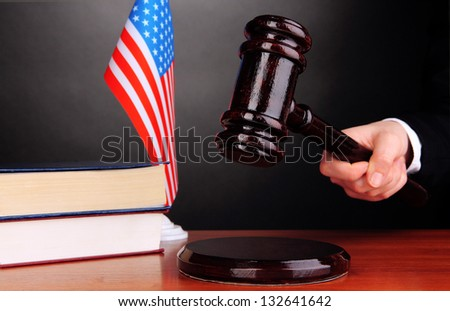 Judge's gavel in hand on grey background - stock photo