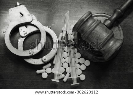 Judge's gavel with handcuffs, drugs and syringes on wooden table, drugs concept - stock photo