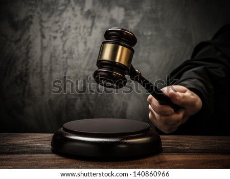Judge's hold hammer on wooden table - stock photo