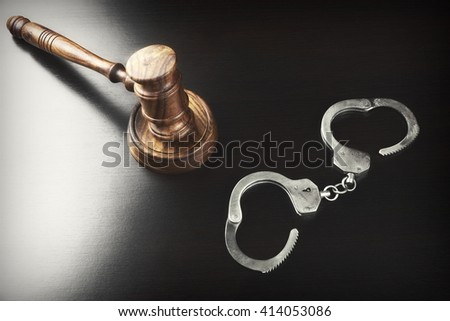 Judges Gavel And Handcuffs On The Black Table In The Back Light. Top View. - stock photo
