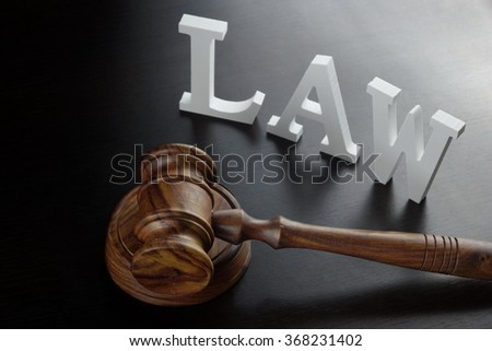 Judges Gavel And White Sign Law Made From Wooden Letter On The Black Wood Table  Background In Back Light, Close Up, Conceptual Image. - stock photo