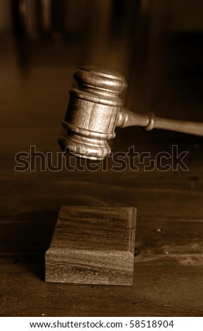 judges gavel  coming down and hitting the block gavel blurred for movement - stock photo