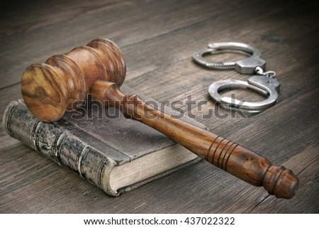 Judges Gavel Or Hammer, Silver Metal Handcuffs and Old Vintage Law Book On Wooden Table In The Courtroom, Law Concept, Close Up - stock photo