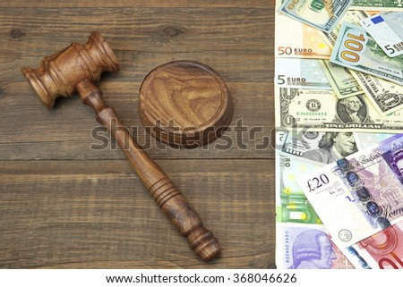 Judges Walnut Gavel And International Money (Dollars, Euro, Pound Sterling) On Rough Wood Background. Overhead View. Conceptual Image - stock photo