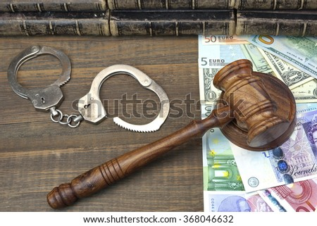 Judges Walnut Gavel, Handcuffs And International Money (Dollars, Euro, Pound Sterling) On Rough Wood Background. Overhead View. Conceptual Image - stock photo