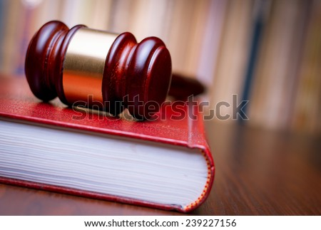 Judges wooden gavel resting on a large red law book on a table in court in a conceptual image of justice and law enforcement - stock photo