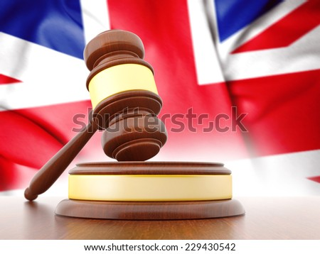 Judges wooden gavel with UK flag in the background - stock photo