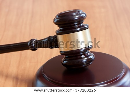 Judicial hammer with a support on a wooden table