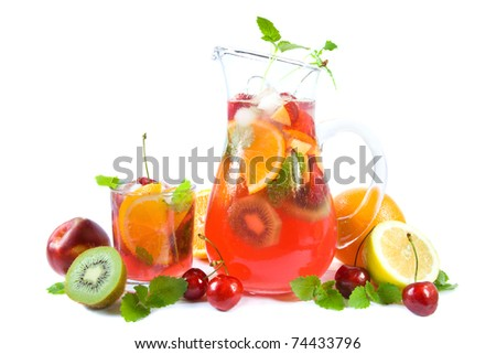 Jug and a drinking glass with colorful summer punch or lemonade and fruits. - stock photo