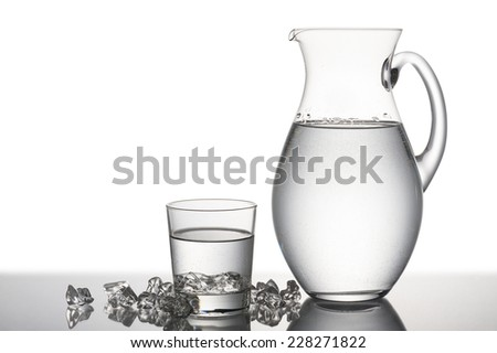 jug and glass full of water with pieces of ice cubes
