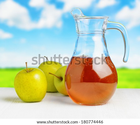 Jug of apple juice on nature background. Half full pitcher.