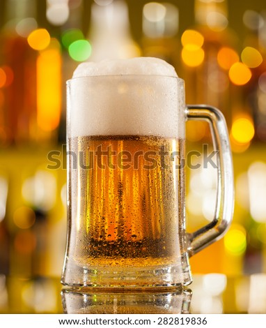 Jug of beer placed on bar counter - stock photo
