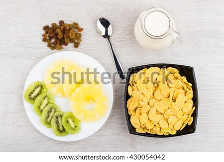 Jug of milk, bowl with corn flakes, pineapple and kiwi in plate and raisins on wooden table. Top view - stock photo