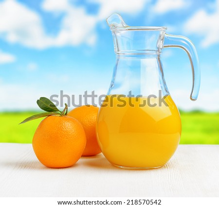 Jug of orange juice on nature background. Half full pitcher. - stock photo