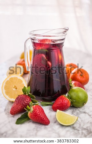 Jug of tasty red sangria with fresh delicious fruits on white marble table: red strawberries, yellow lemons, green limes and orange mandarins