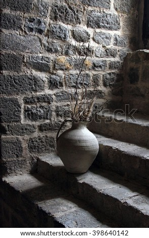 Jug on stone stairs in the fortress at Montalcino, Italy