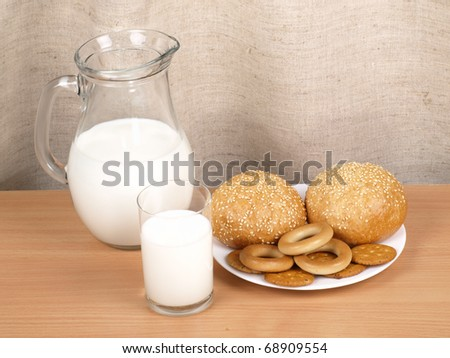 Jug with milk and loaves on by a kitchen table - stock photo