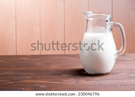 jug with milk on a light wooden table side view - stock photo