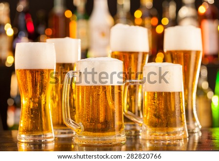 Jugs of beer placed on bar counter with copy space - stock photo