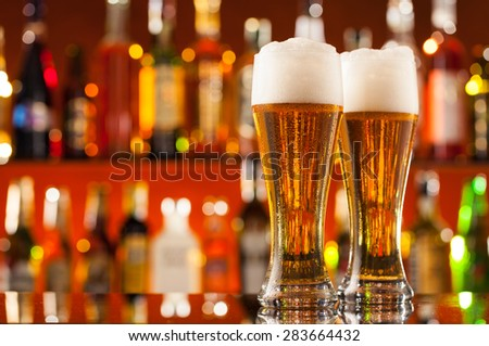 Jugs of beer placed on bar counter with free space for text - stock photo