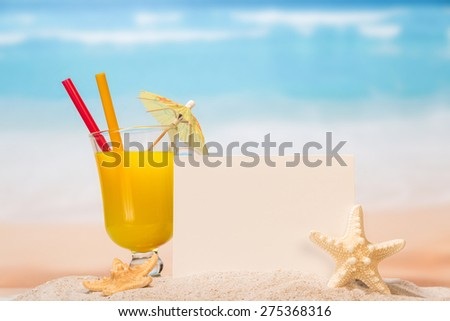 Juice in the glass, blank paper and starfish in the sand - stock photo