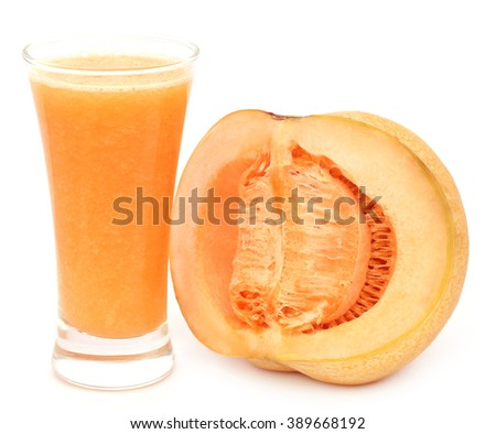 Juice of cucumis melo or muskmelon in a glass with sliced fruit - stock photo