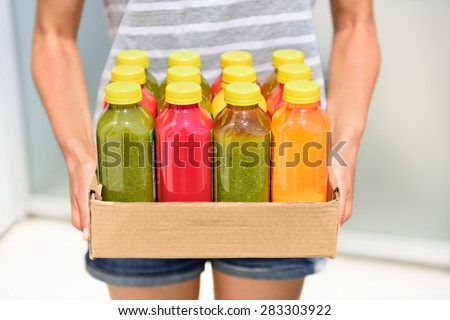 Juicing cold pressed vegetable juices for a detox diet. Dieting by cleansing your body from toxins with raw organic fruits and vegetables juice made fresh and delivered in bottles. - stock photo