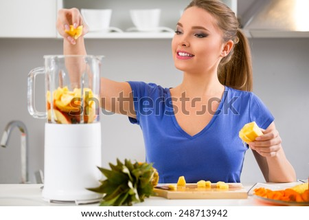 Juicing-woman making fruit juice using juicer machine at home in kitchen - stock photo