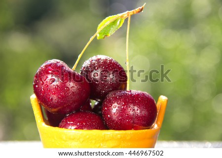 Juicy and ripe cherry in ceramic basket with water drops - stock photo