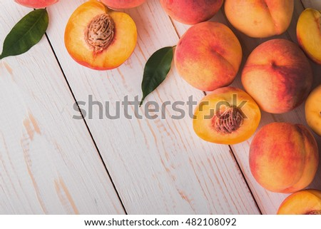 juicy and ripe peach fruits on white wood table