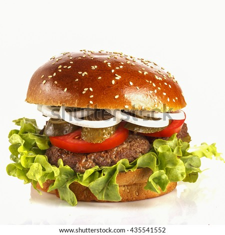 Juicy, appetizing burger with pickled cucumber, tomato and onion.