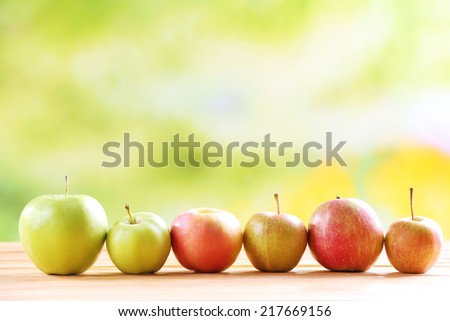 Juicy apples in row on table on bright background - stock photo