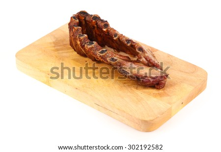 juicy barbecued pork ribs on cutting board isolated on white background