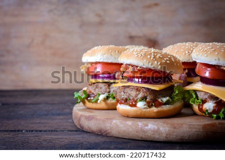 Juicy beef burgers on wooden background and the blank space on left side  - stock photo