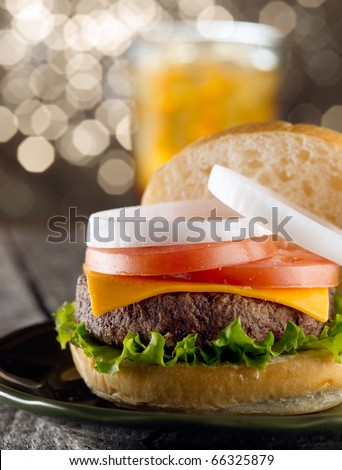 juicy cheeseburger with drink in background. (note-selective focus) - stock photo
