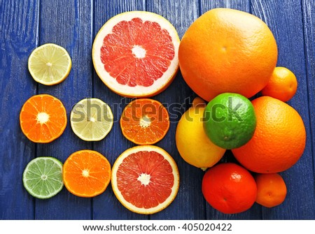 Juicy composition of sliced citrus on blue wooden background - stock photo