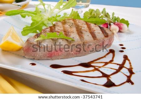 Juicy delicious Citrus-peppercorn-spiked grilled tuna steak with grilled vegetables - stock photo