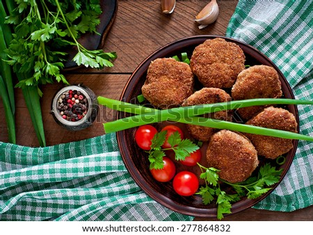 Juicy delicious meat cutlets on a wooden table in a rustic style. Top view. - stock photo