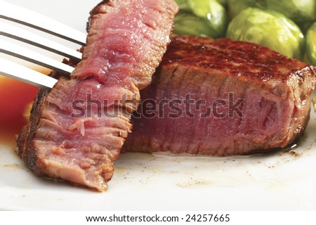 juicy filet mignon cutted on plate with brussel sprout - stock photo