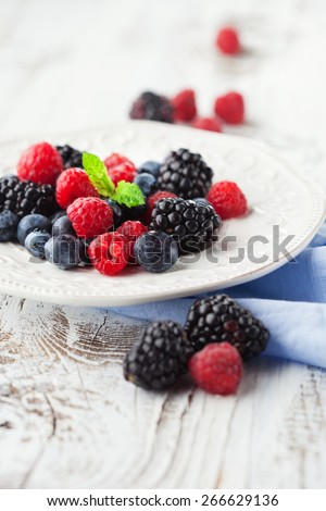 Juicy fresh blueberries, raspberries and blackberries in a plate on white wooden background, selective focus