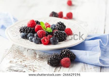 Juicy fresh blueberries, raspberries and blackberries in a plate on white wooden background, selective focus - stock photo