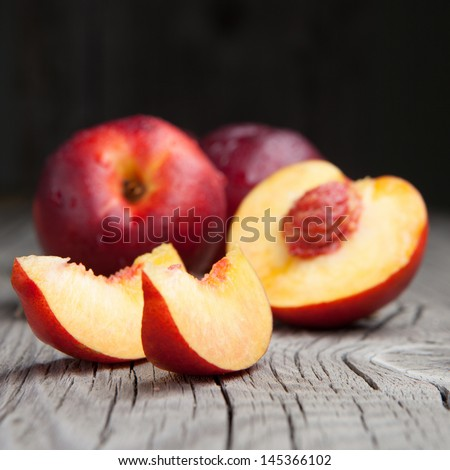 Juicy fresh peaches on a dark wooden background - stock photo